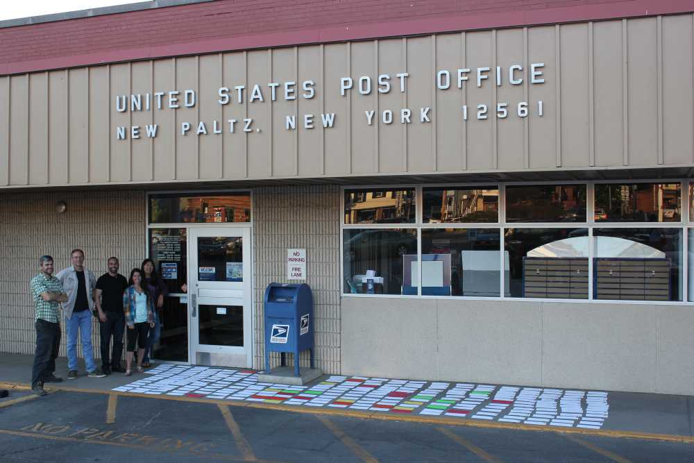 Members of the GCC Board of Directors in front of the post office with hundreds of letters laid out.