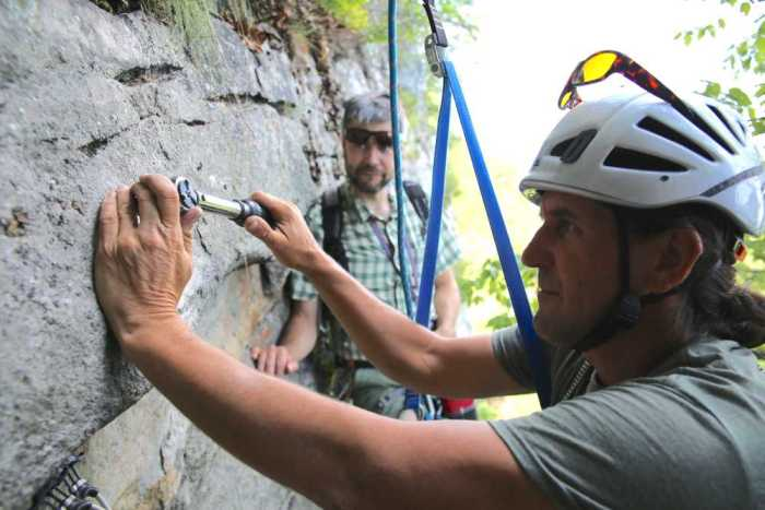 Mohonk Preserve Ranger Frank Tkac installed a new bolted rap anchor; Christian Fracchia watches.