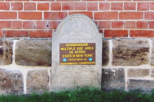 Tombstone with the sign of the Shawangunk Multiple Use Area (MUA), the campground is closing soon.