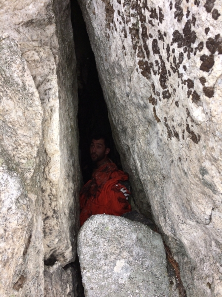 Braxton retrieving trash in a crevice at Bonticou Crag in the Mohonk Preserve, for the Gunks Climbers' Coalition Adopt-A-Crag day clean up.