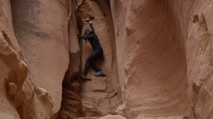 "Still of woman climbing in a canyon, from the video ""My Desolate Eden,"" part of the No Man's Land Film Festival."