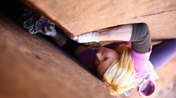 "Woman climbing a big off width crack, a still from the video ""Finding Wide"" from the No Man's Land Film Festival."