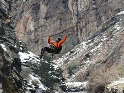 Chris Vultaggio doing tyrolean traverse over a river.