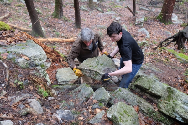 Moving heavy rocks to build steps on the new trail to the Sleepy Hollow area of the Gunks. GCC & SUNY New Paltz Outing Club trail work day, April 2019, Mohonk Preserve.