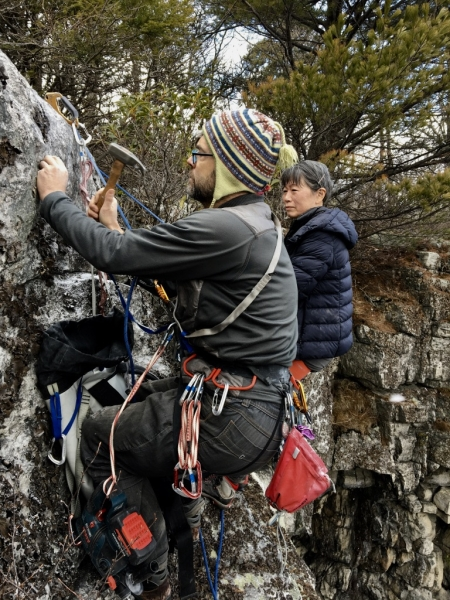 Christian Fracchia installing bolt anchors at the top of the Antlion Cliff.
